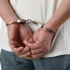 Criminal in handcuffs representing online crime